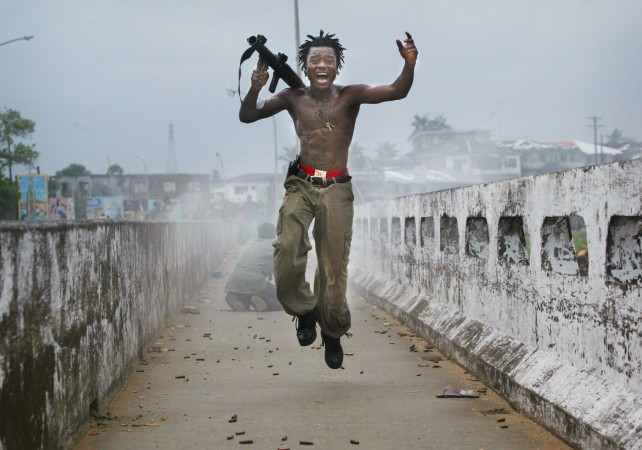 Joseph Duo, a Liberian militia commander, jumps for joy after firing a rocket-propelled grenade at rebel forces in Monrovia, Liberia, on July 20, 2003. (Chris Hondros/Getty Images)