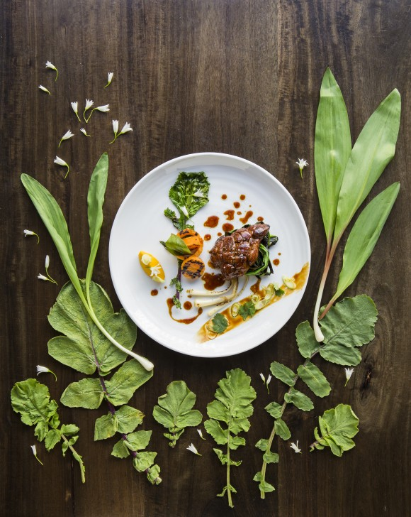 Foraged ramps, white mustard, and wild onion flowers make their way into a dish with sweetbreads and roasted sweet potatoes, at Racines NY in Manhattan. (Samira Bouaou/The Epoch Times)