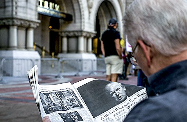 A man reads an article by The New York Times on Donald Trump during a protest outside the new Trump International Hotel at the old post office in Washington on Oct. 26, 2016. (Gabriella Demczuk/Getty Images)