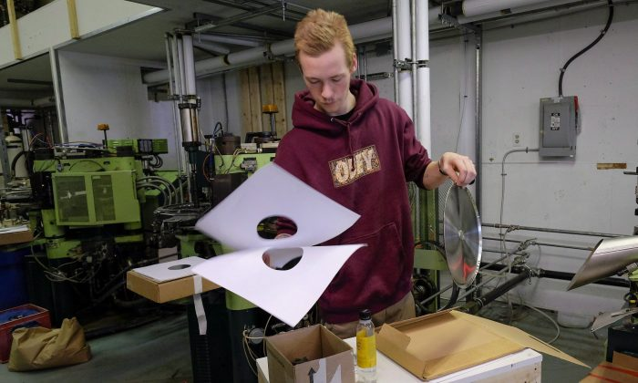 Jake Scott-Reid works on making a vinyl record at Canada Boy Vinyl, the only vinyl record factory in Canada, in Calgary, Alta., Oct. 28, 2015. (THE CANADIAN PRESS/Jeff McIntosh)