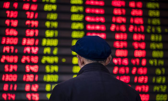 An investor looks at an electronic board showing stock information at a brokerage house in Shanghai on March 16, 2017. (Johannes Eisele/AFP/Getty Images)