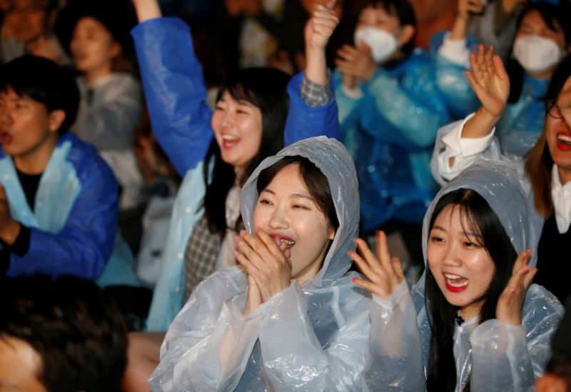 Supporters of presidential candidate Moon Jae-in react as they watch a television broadcast of the presidential election exit polls result in Seoul, South Korea on May 9, 2017. (REUTERS/Kim Kyung-Hoon)