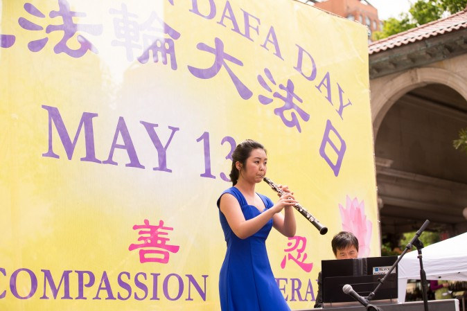 Lleana Feng plays the Oboe during the World Falun Dafa Day event at Union Square, New York City, on May 11, 2017. (Benjamin Chasteen/The Epoch Times)