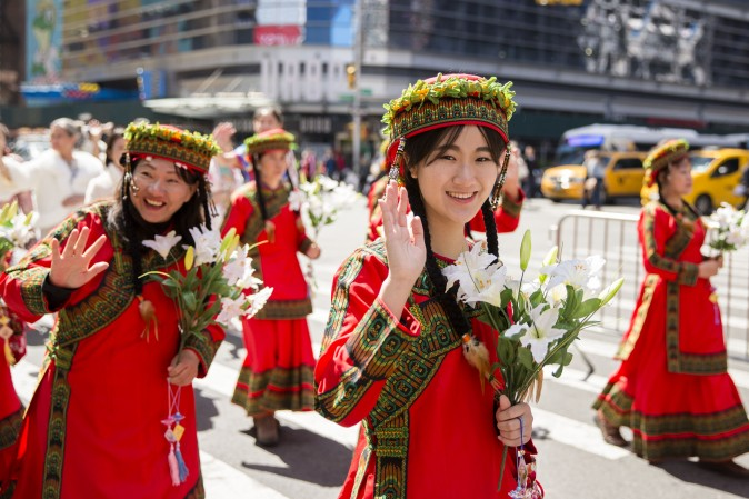 Falun Gong practitioners wearing ethnic Chinese clothes, march in a parade along 42nd Street in New York for World Falun Dafa Day on May 12, 2017. (Samira Bouaou/The Epoch Times)