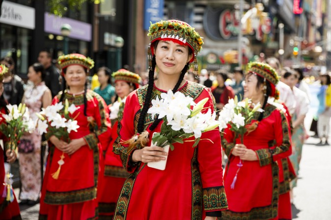 Falun Dafa practitioners wearing ethnic Chinese clothes, march in a parade along 42nd Street in New York for World Falun Dafa Day on May 12, 2017. Mr. Li Hongzhi, the founder of Falun Dafa, gave his first lecture 25 years ago on May 13 in his native city of Changchun in China. Today, Falun Dafa is practiced by tens of millions in over 70 countries. (Samira Bouaou/The Epoch Times)