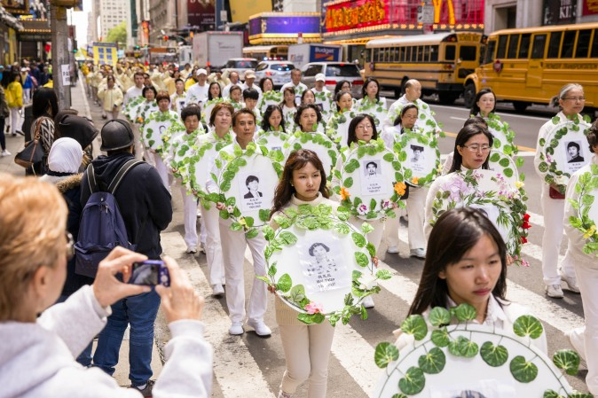 Falun Gong practitioners hold wreaths with photos of people who were killed inside China for their beliefs during the World Falun Dafa Day parade in New York on May 12, 2017. (Samira Bouaou/The Epoch Times)