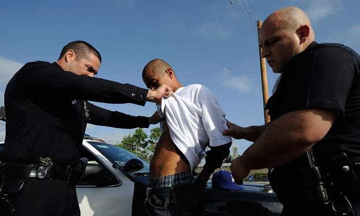 """Los Angeles Police Department officers from the 77th Street division detain a twenty-year old """"Street Villains"""" gang member who was recently released from prison  in Los Angeles, Calif., on April 29, 2012. (Kevork Djansezian/Getty Images)"""