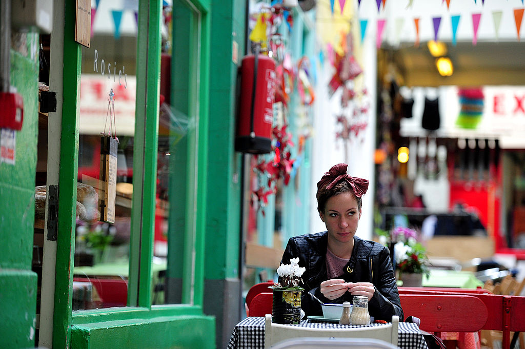 A woman relaxes at a cafe in Brixton Village, south London, on Oct. 17, 2013. (CARL COURT/AFP/Getty Images)