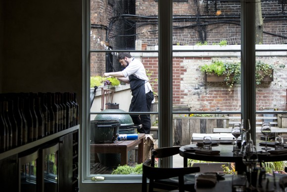 Sous chef James Evangelinos picks herbs from the garden in the back of the restaurant. (Samira Bouaou/The Epoch Times)