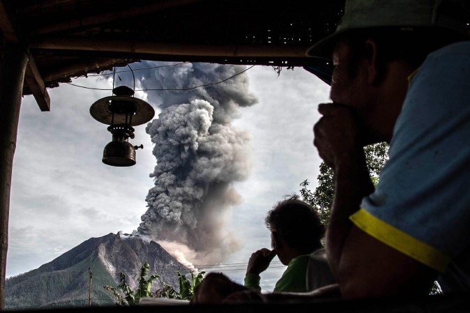 Villagers look on as Mount Sinabung volcano spews thick volcanic ash in Karo Regency, Indonesia, on May 19, 2017. Sinabung roared back to life in 2010 for the first time in 400 years. (IVAN DAMANIK/AFP/Getty Images)