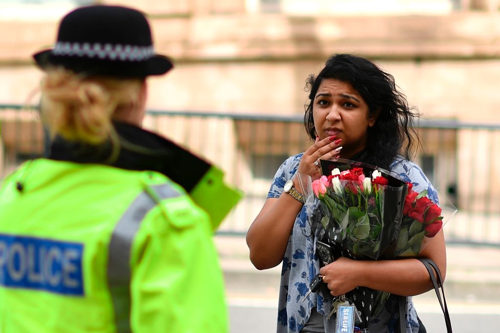 A police officer (L) talks with a woman carrying a bunch of flowers near the Manchester Arena in Manchester, northwest England on May 23, 2017. (BEN STANSALL/AFP/Getty Images)