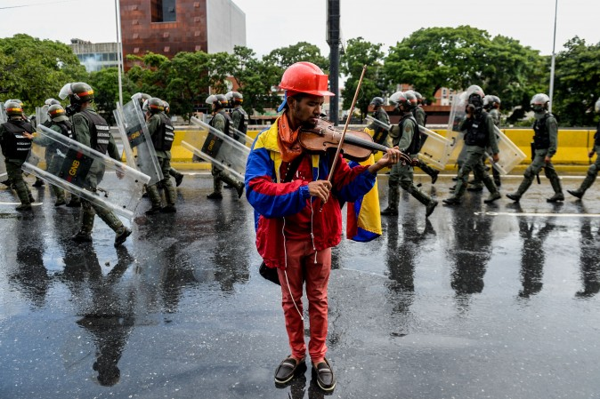 An opposition demonstrator plays the violin during a protest against President Nicolas Maduro in Caracas, Venezuela, on May 24, 2017. Venezuela's President Nicolas Maduro formally launched moves to rewrite the constitution on Tuesday, defying opponents who accuse him of clinging to power in a political crisis that has prompted deadly unrest. (FEDERICO PARRA/AFP/Getty Images)