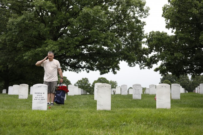 A volunteer salutes after laying a rose before a headstone at Arlington National Cemetery in Arlington, Va., on May 28, 2017. Volunteers from throughout the country gather to place a rose at each grave in preparation for Memorial Day. (Aaron P. Bernstein/Getty Images)