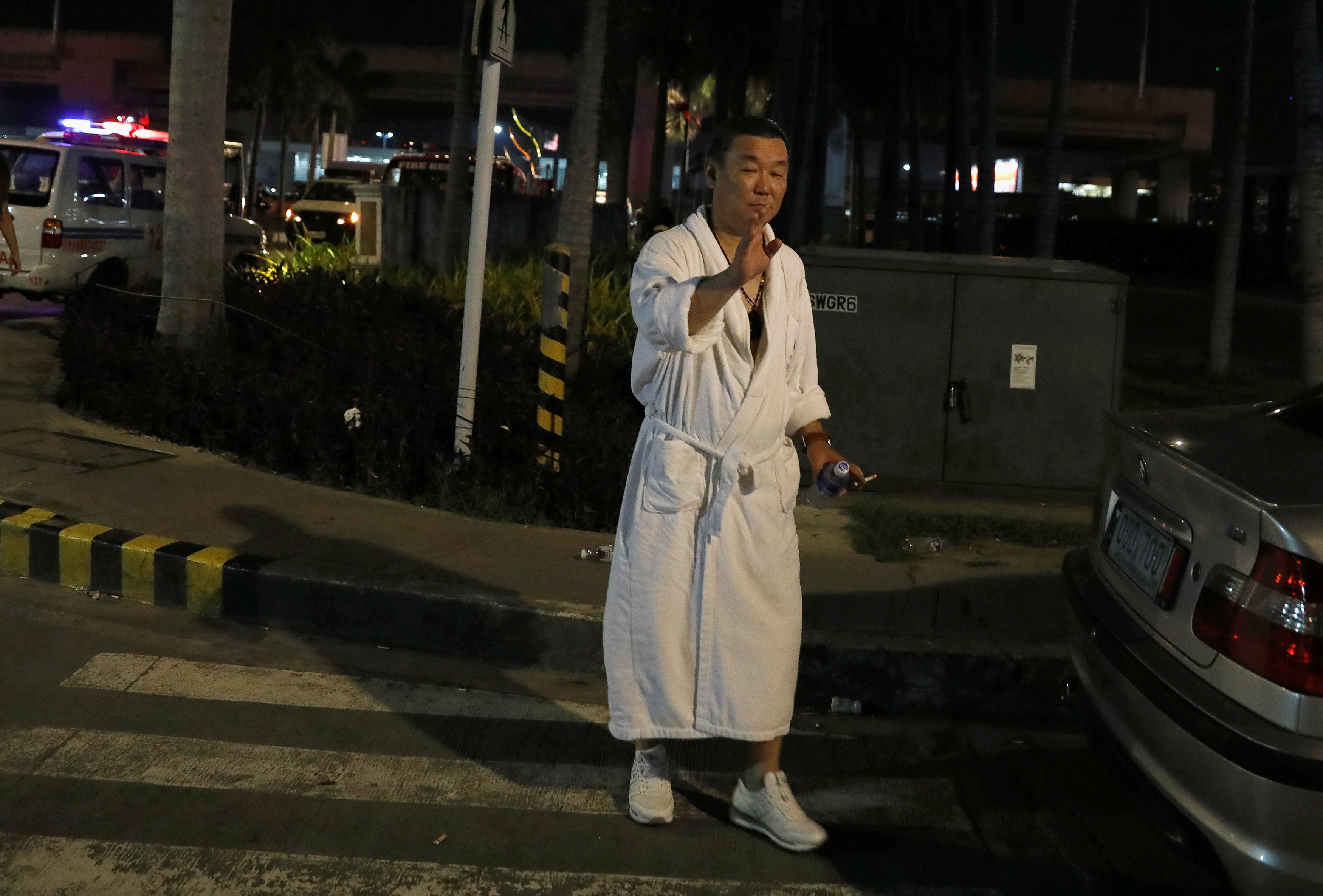 A tourist wearing a bathrobe gestures after he was evacuated from the Resorts World Manila after gunshots and explosions were heard in Pasay City, Metro Manila, Philippines on June 2, 2017. (REUTERS/Erik De Castro)