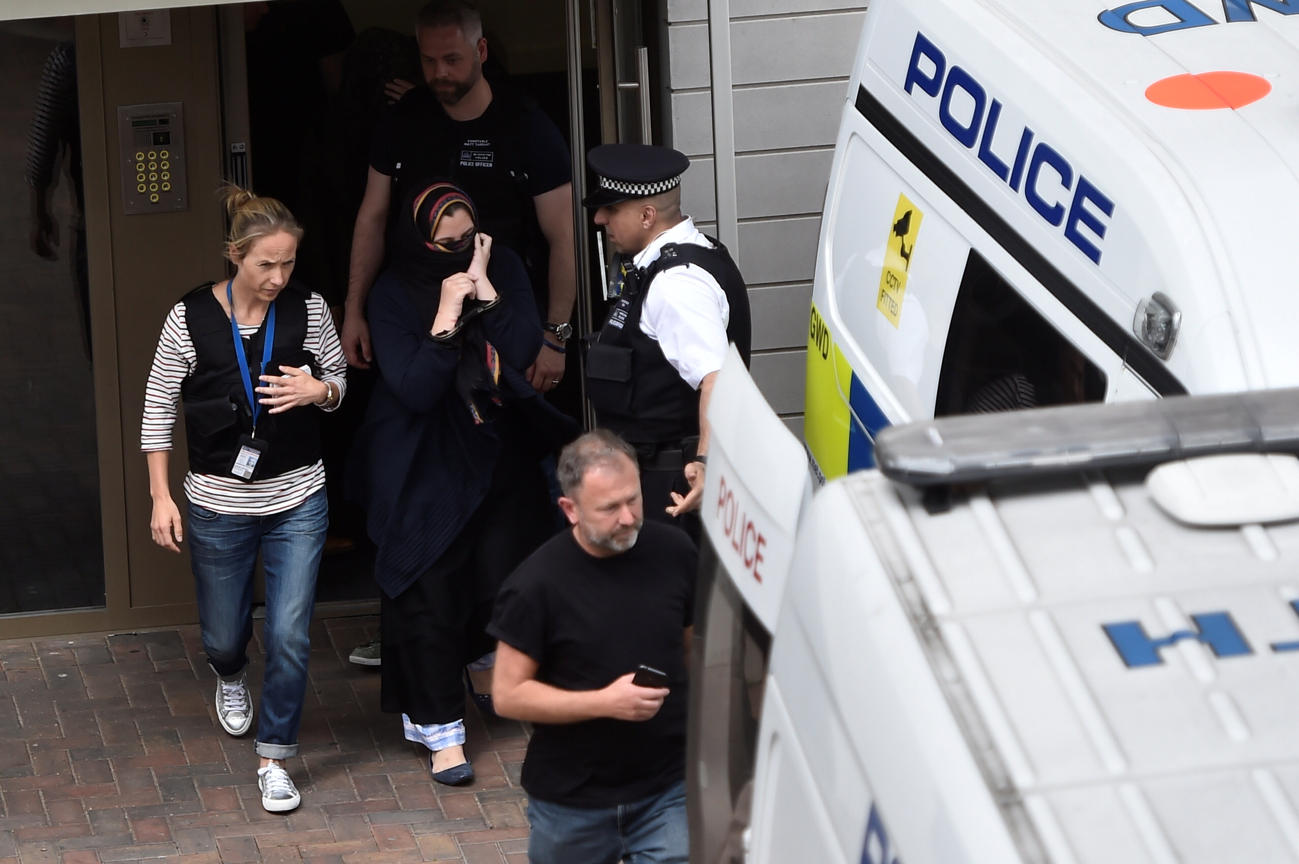 Police officers escort a woman to a police van after raiding a block of flats in Barking, east London, Britain on June 4, 2017. (REUTERS/Hannah McKay)