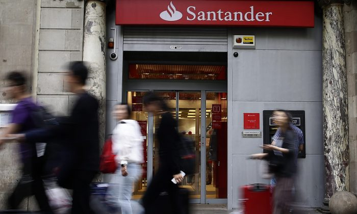 People walk past aBancoSantanderoffice in Barcelona on June 7, 2017. Spain'sBancoSantanderhas acquiredBanco Popular, the troubled lender that lost more than half of its shares value over the past week. (AP Photo/Manu Fernandez)