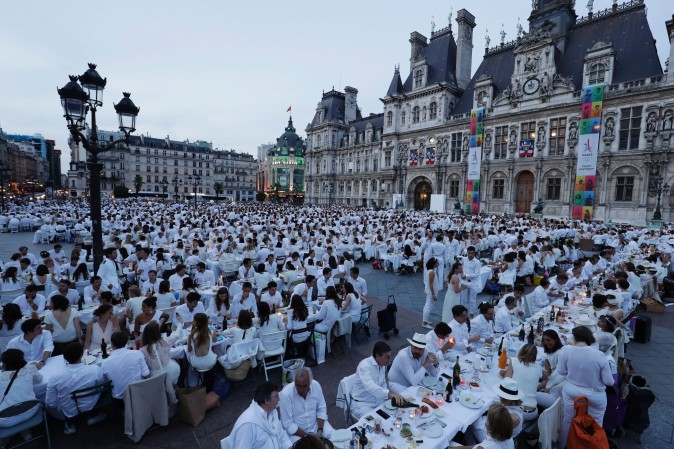 "Participants dressed in white attend a ""Diner en Blanc"" (Dinner in White) in front of the City Hall in Paris on June 8, 2017. Diner en Blanc, the most chic picnic gathering thousands of participants, takes place every year at a surprise location disclosed at the last minute to the participants. (THOMAS SAMSON/AFP/Getty Images)"