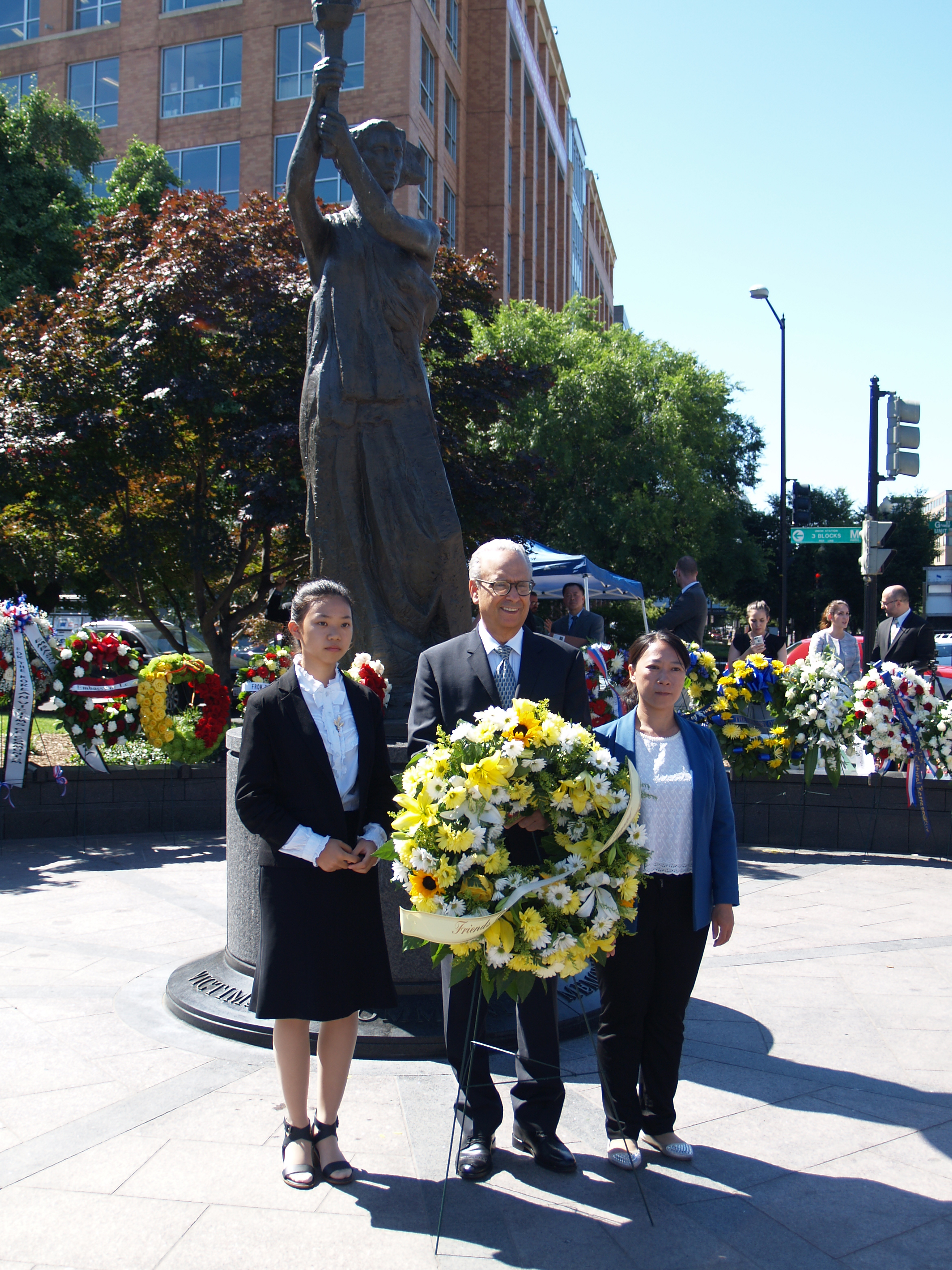 Xu Xinyang (L), Alan Adler, and Chi Lihua present a wreath remembering the victims of communism at the tenth annual Truman-Reagan Medal of Freedom and Roll Call of Nations Ceremony, on June 9 in Washington, D.C. Adler is the executive director of Friends of Falun Gong, Xu and Li are practitioners of Falun Gong who suffered persecution in China for their beliefs. (Kitty Wang, NTDTV)