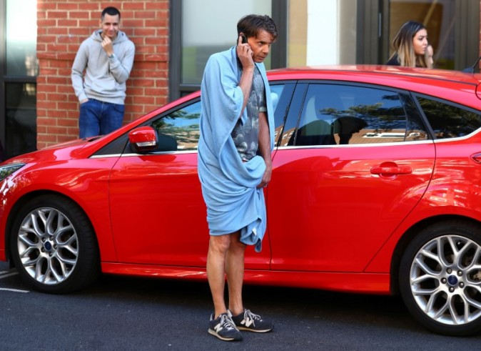 A man wrapped in a towel speaks on a cell phone near the scene of a fire in a tower block, in West London, Britain on June 14, 2017. (REUTERS/Neil Hall)