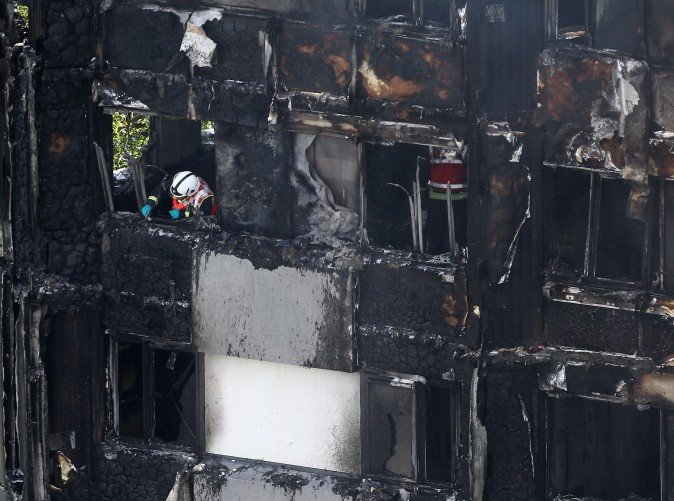 A firefighter examines material in a tower block severely damaged by fire in West London, Britain on June 14, 2017. (REUTERS/Neil Hall)