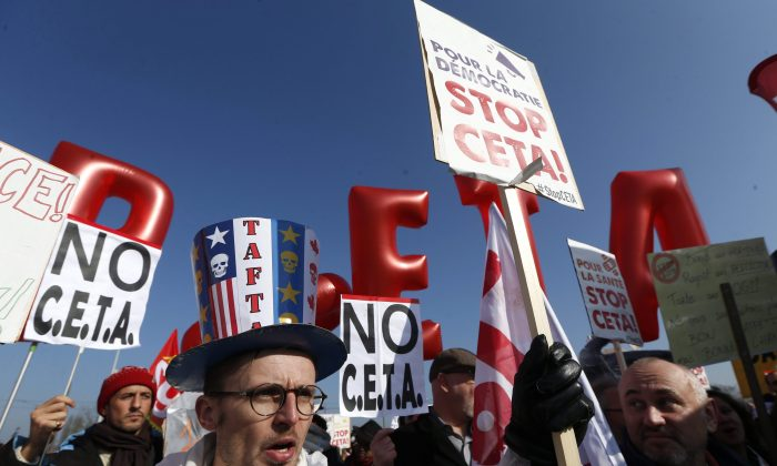 Demonstrators march against the CETA trade deal near the European Parliament in Strasbourg, France on Feb.15, 2017. Globalization has not been kind to incomes of most of the middle class in developed world economies. (AP Photo/Jean-Francois Badias)