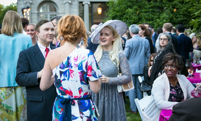Alexis Light, senior manager of media relations and marketing for The Frick (front), speaks with artist Annika Connor and another guest in The Frick's Fifth Avenue Garden during the Spring Garden Party for Fellows of The Frick Collection on June 7. (Benjamin Chasteen/The Epoch Times)