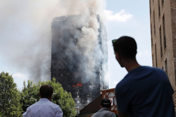 Pedestrians look up towards Grenfell Tower, a residential block of flats in west London on June 14, 2017, as firefighters continue to control a fire that engulfed the building in the early hours of the morning. Shaken survivors of a blaze that ravaged a west London tower block told Wednesday of seeing people trapped or jump to their doom as flames raced towards the building's upper floors and smoke filled the corridors.   / AFP PHOTO / Adrian DENNIS        (Photo credit should read ADRIAN DENNIS/AFP/Getty Images)