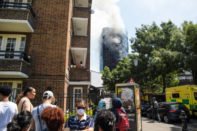LONDON, ENGLAND - JUNE 14:  People look on as smoke rises from the burning building after a huge fire engulfed the 24 storey residential Grenfell Tower block in Latimer Road, West London in the early hours of this morning on June 14, 2017 in London, England. The Mayor of London, Sadiq Khan, has declared the fire a major incident as more than 200 firefighters are still tackling the blaze while at least six are dead and 20 are in critical care. (Photo by Jack Taylor/Getty Images)