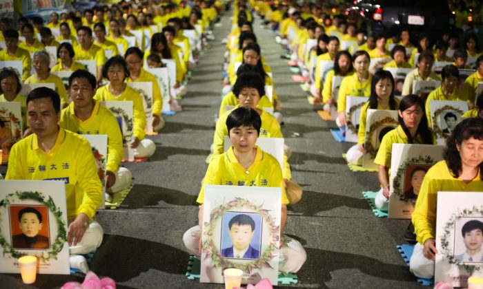 Falun Gong practitioners hold a candlelight vigil in front of the Chinese Consulate in Los Angeles on Oct. 15, 2105, for those who have died during the 16 year persecution in China. They demand that Jiang Zemin be brought to justice. (Benjamin Chasteen/Epoch Times)