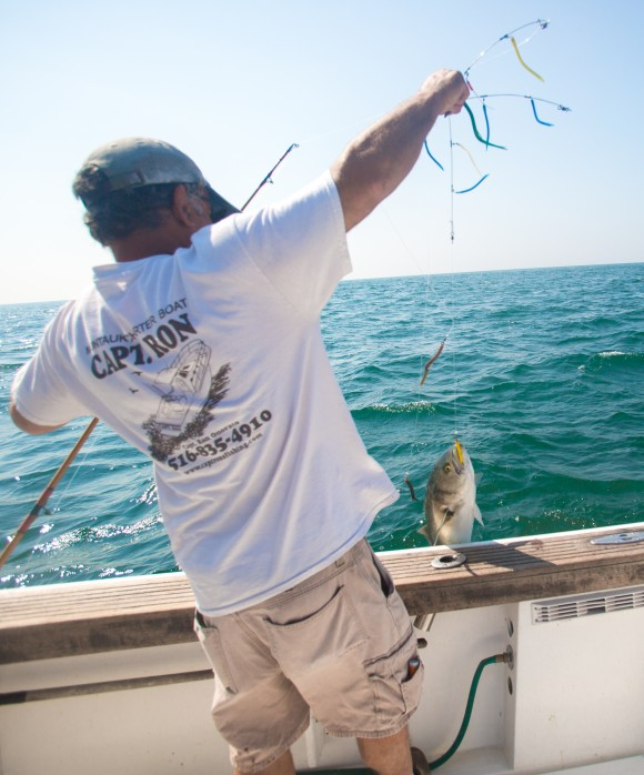 Onorato uses his fishing contraption to successfully bait a bluefish. (Benjamin Chasteen/Epoch Times)