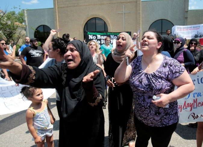 A group of women react as they talk about family members seized on Sunday by Immigration and Customs Enforcement agents in Southfield, MI, on June 12, 2017. (Rebecca Cook/Reuters)