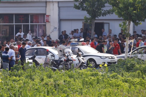 Onlookers and security personnel gather near the scene of an explosion at a kindergarten in Fengxian County in Jiangsu Province, China June 16, 2017. (Reuters/Aly Song)