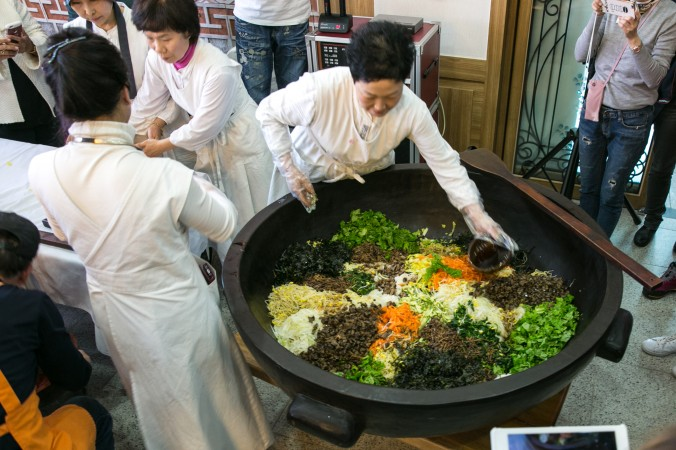 Chefs make bibimbap for all the guests using a large cast iron cooking pot.   (Benjamin Chasteen/The Epoch Times)