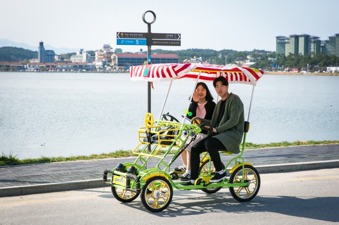 A couple rides a surrey bike around Gyeongpoho Lake during the Gyeongpo Cherry Blossom Festival in Gangneung.  (Benjamin Chasteen/The Epoch Times)