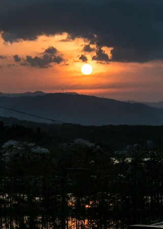"""The sun sets over mountains and  Gyeongpoho (""""clear as a mirror"""") Lake in the  eastern city of Gangneung. (Benjamin Chasteen/The Epoch Times)"""