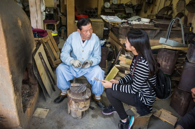 A worker explaining the process of making traditional tools at the Korean Folk Village. (Benjamin Chasteen/The Epoch Times)