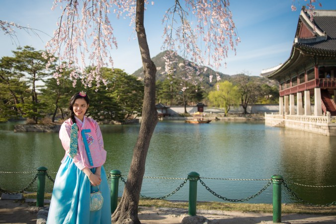 A woman has her photo taken next to the picturesque pavilion in the Gyeongbokgung Palace. (Benjamin Chasteen/The Epoch Times)