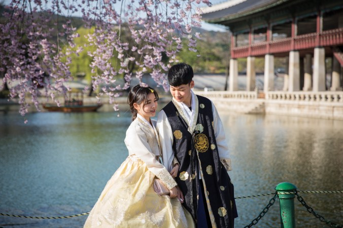 A couple wears traditional Korean clothing while visiting the Gyeonghoeru Pavilion at  the Gyeongbokgung Palace in Seoul. (Benjamin Chasteen/The Epoch Times)