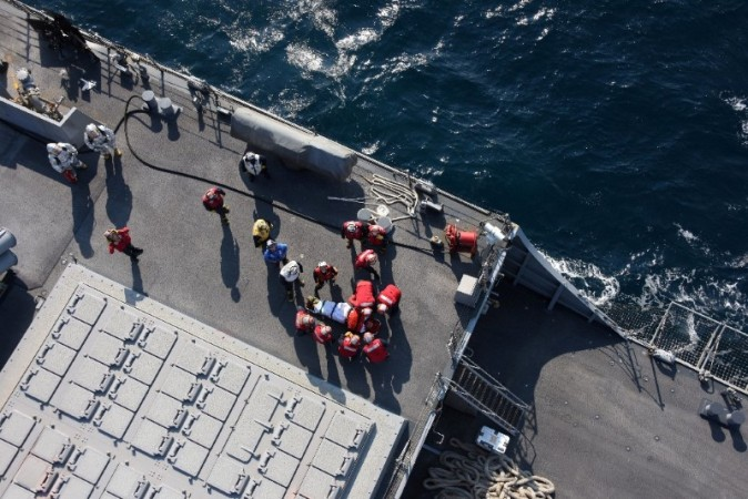 An injured crew member (C) of the Arleigh Burke-class guided-missile destroyer USS Fitzgerald, damaged after colliding with a Philippine-flagged merchant vessel, is carried on a stretcher on the destroyer off Shimoda, Japan June 17, 2017.  Japan Maritime Self-Defense Force/Handout via REUTERS