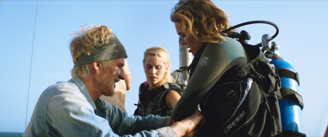 (L–R) Kate (Claire Holt) and Lisa (Mandy Moore) suit-up with the help of Captain Taylor (Matthew Modine) for an unforgettable underwater shark dive  in