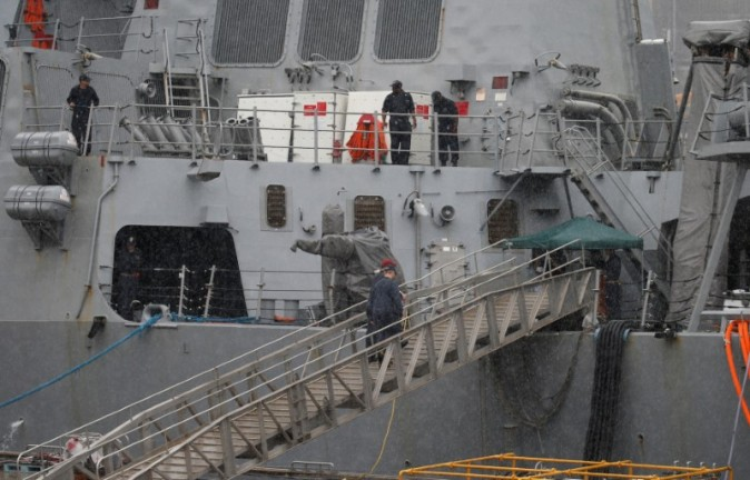 Personnel are seen on the Arleigh Burke-class guided-missile destroyer USS Fitzgerald which has been damaged by colliding with a Philippine-flagged merchant vessel, at the U.S. naval base in Yokosuka, Japan, June 18, 2017. (Reuters/Toru Hanai)