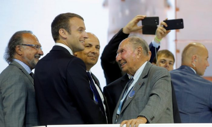 French President Emmanuel Macron (2ndL) talks with Dassault Aviation CEO Eric Trappier (C) as Serge Dassault (2ndR), Chairman and CEO of Dassault Group, during a visit at the Paris Air Show in Le Bourget, north of Paris, France on June 19, 2017. (REUTERS/Michel Euler/Pool)