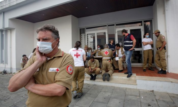 Red Cross and other relief personnel are seen outside a relief centre for people affected by a forest fire in Figueiro dos Vinhos, Portugal on June 19, 2017. (REUTERS/Miguel Vidal)