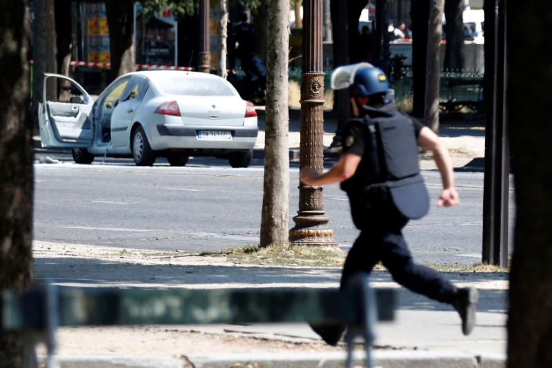A French gendarme runs past a car on the Champs Elysees avenue after an incident in Paris, France on June 19, 2017. (REUTERS/Charles Platiau)