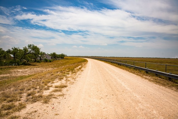 The levee road behind the tiny border town of Granjeno, Texas, on May 28, 2017. The levee drops about 18 feet to the right, and Granjeno is situated to the left. (Benjamin Chasteen/The Epoch Times)