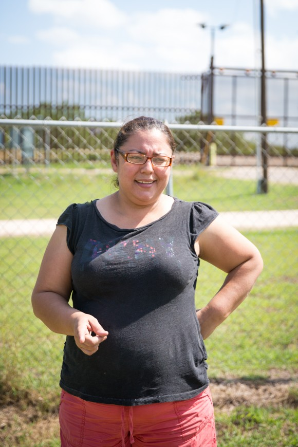 Noelia Guerra in her yard with the border fence behind her in Brownsville, Texas, on June 1, 2017. She has seen many illegal immigrants scale the 18-foot fence and hide in the trees behind her property.  (Benjamin Chasteen/The Epoch Times)