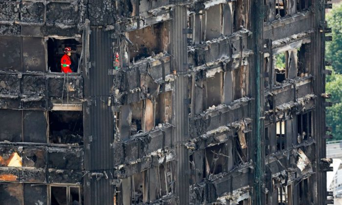 Members of the emergency services work on the middle floors of the charred remnains of the Grenfell Tower block in Kensington, west London, on June 17, 2017, follwing the June 14 fire at the residential building. (Tolga Akmen/AFP/Getty Images)