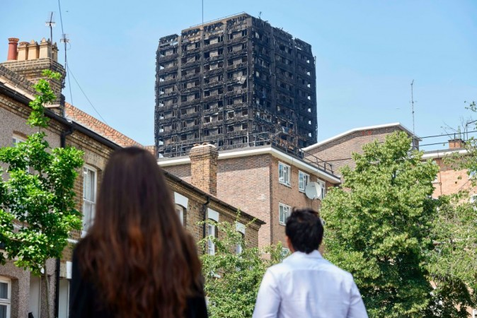 The burned-out shell of the Grenfell Tower block is seen behind terraced houses as local residents look on near the scene of the fire in North Kensington, west London on June 20, 2017. (Niklas Halle'n/AFP/Getty Images)