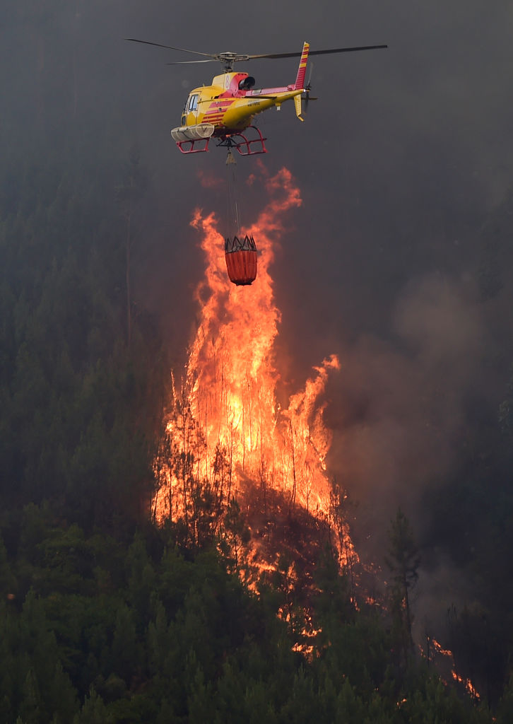 A helicopter overfly a wildfire in Carvalho, next to Pampilhosa da Serra, on June 19, 2017. (MIGUEL RIOPA/AFP/Getty Images)