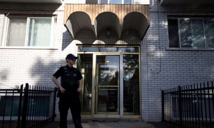 A police officer stands outside the home of Amor Ftouhi, in Montreal, Quebec, Canada on June 21, 2017. (REUTERS/Christinne Muschi)